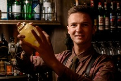 portrait of smiling man bartender holding glassy shaker with cocktail in his hands and shakes it