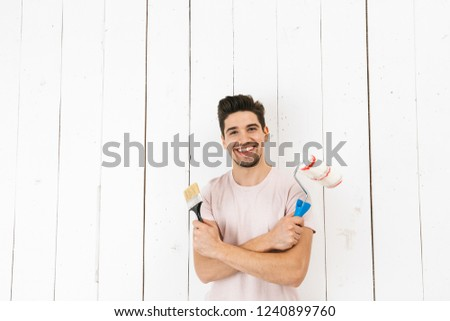 Portrait of smiling man 20s holding paint roller and brush while painting white wall and making renovation #1240899760