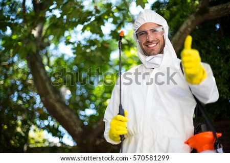 Portrait of smiling man showing thumbs up while holding insecticide sprayer in lawn