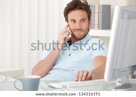 Portrait of smiling man speaking on mobile phone, sitting at desk, looking at computer screen.
