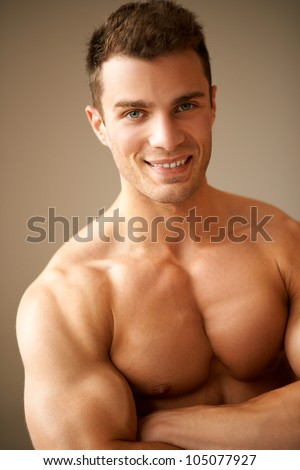 Portrait of smiling man with muscular arms crossed