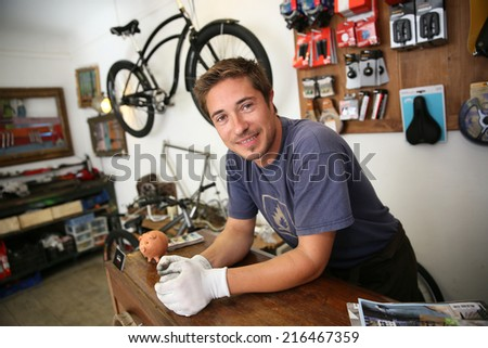 Portrait of smiling man working in bike rental shop