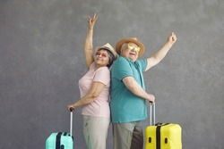 Portrait of smiling married senior couple with suitcases standing back to back on gray studio background. Happy old retired travelers having fun before holiday trip. Summer vacation, traveling concept