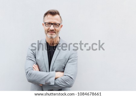 Portrait of smiling mature bearded man wearing glasses standing with arms crossed against bright background