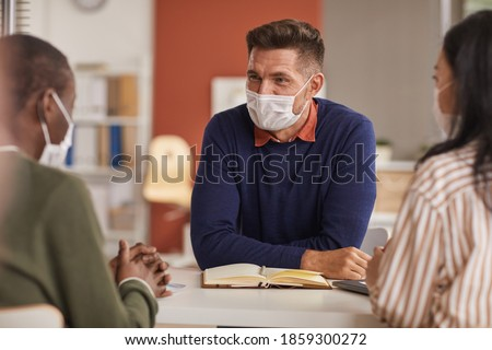 Portrait of smiling mature businessman wearing mask during business meeting in office, copy space
