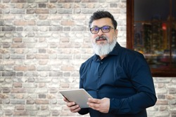 Portrait of smiling mature businessman with spectacles holding digital tablet while looking at camera – Confident multiethnic satisfied man in creative office – Successful middle eastern business man