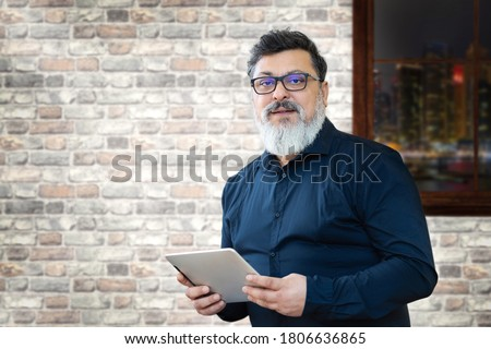 Portrait of smiling mature businessman with spectacles holding digital tablet while looking at camera – Confident multiethnic satisfied man in creative office – Successful middle eastern business man Stock photo ©