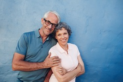 Portrait of smiling mature couple standing together against blue background. Happy middle aged man and woman against a wall.