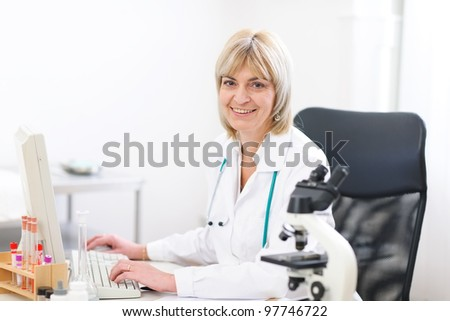 Portrait of smiling mature doctor woman at laboratory - stock photo
