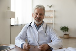 Portrait of smiling mature male physician or GP in white medical uniform sit at desk in hospital, happy senior man doctor or therapist with stethoscope pose at workplace, medicine, healthcare concept