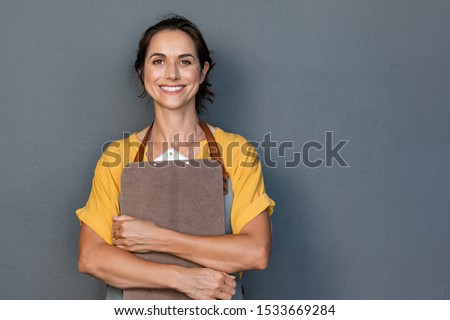 Portrait of smiling mature woman in apron holding clipboard and looking at camera. Beautiful waitress isolated on grey wall with copy space. Successful small business owner standing on grey background