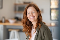 Portrait of smiling mature woman looking at camera with big grin. Successful middle aged woman at home smiling. Beautiful mid adult lady with long red hair enjoying whitening teeth treatment.