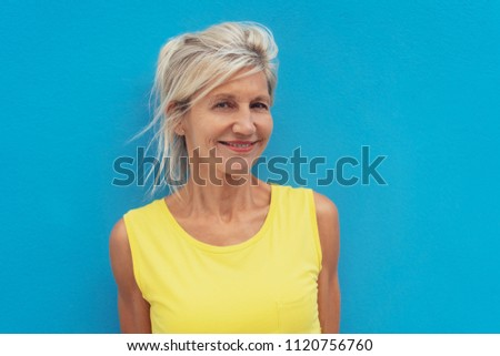 Portrait of smiling mature woman wearing yellow dress posing against blue background