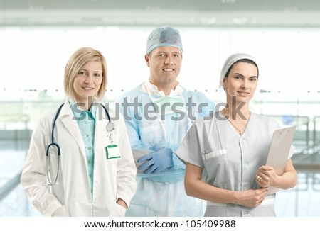 Portrait of smiling medical team of doctor, surgeon and nurse looking at camera on hospital corridor.