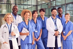 Portrait Of Smiling Medical Team Standing In Modern Hospital Building