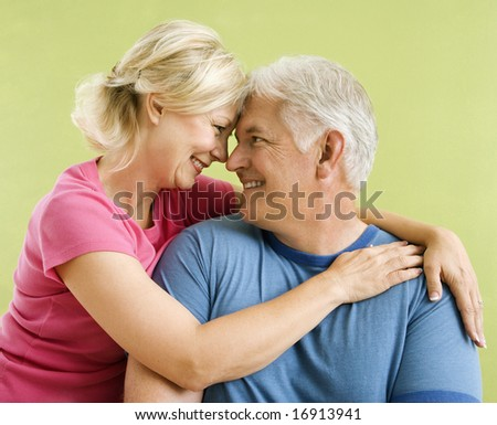 Portrait of smiling middle-aged couple in front of green wall snuggling.