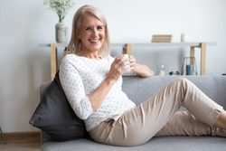 Portrait of smiling middle-aged female retiree sit relax on cozy couch at home enjoy hot beverage, happy mature woman grandmother rest on comfortable sofa drink coffee or tea, look at camera posing