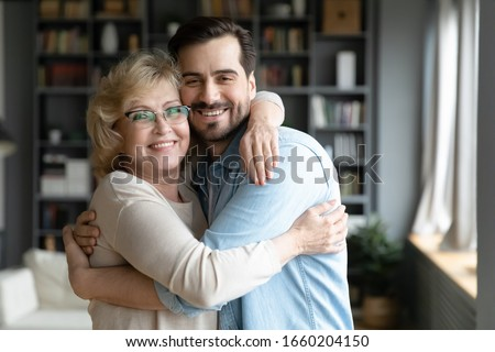 Portrait of smiling middle-aged mother hug cuddle adult son relax in living room together, happy senior 70s mom embrace grown-up man child enjoy family weekend reunion at home, bonding concept
