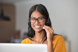 Portrait of smiling middle eastern customer support operator looking at camera. Young indian woman working from home with headset for a call center. Girl in video conference: smart working concept.