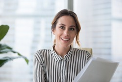 Portrait of smiling millennial businesswoman holding documents looking at camera, headshot of happy woman worker or female ceo posing with paperwork making picture at corporate close up photoshoot.