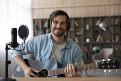 Portrait of smiling millennial Caucasian male singer or composer hold guitar record new single at home studio. Happy young 20s man artist compose song play on electric music instrument. Hobby concept.