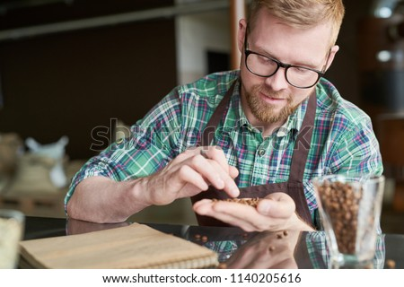 Portrait of smiling modern barista holding handful of fresh coffee beans and checking quality of roast in artisan roastery, copy space