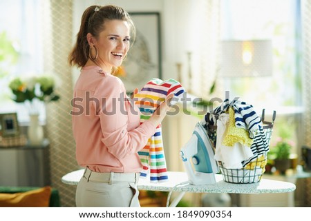 Portrait of smiling modern woman in pink shirt and white pants with iron and washed clothes basket ready to iron in the modern house in sunny day. Photo stock ©
