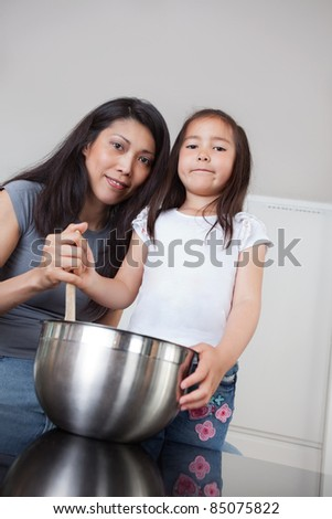 Portrait of smiling mother and cute little daughter in kitchen