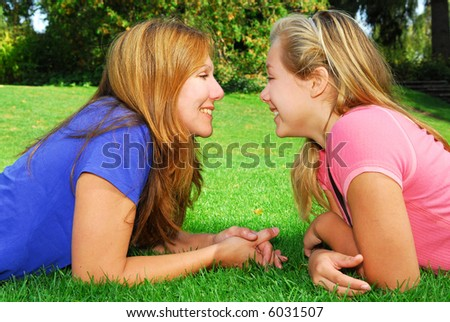 Portrait of smiling mother and daughter in summer park looking at each other