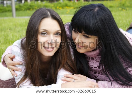 Portrait of smiling mother and teenage daughter hugging in the park happy