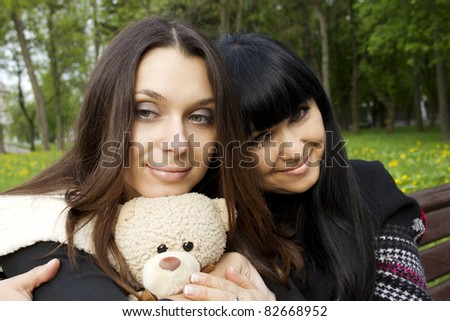Portrait of smiling mother and teenage daughter hugging Teddy bears in the park