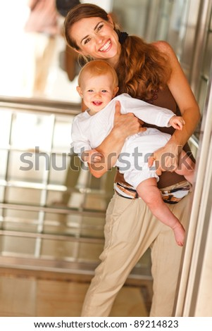 Portrait of smiling mother with baby looking out from elevator