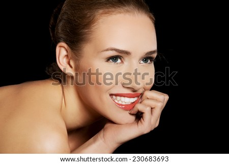 Portrait of smiling nude woman on dark background.
