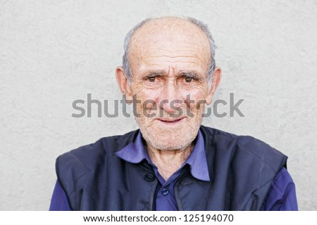 Portrait of smiling old hoary man in blue shirt