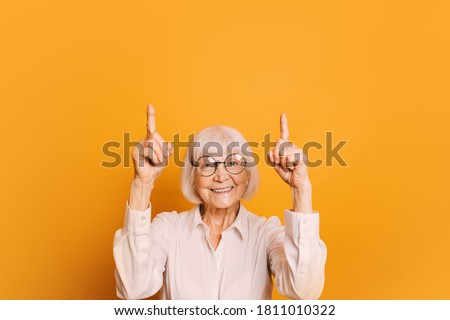 Portrait of smiling old woman with short gray hair and round glasses wearing white blouse, pointing fingers up. Senior woman isolated over orange background