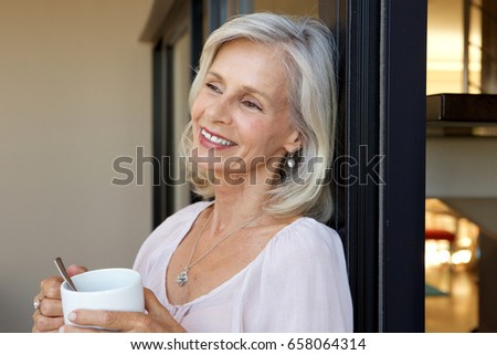 Portrait of smiling older woman standing with cup of coffee