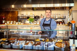 Portrait of smiling owner standing at his eatery serving food behind counter – young entrepreneur wearing apron running small restaurant – happy man working