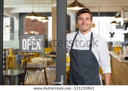 Portrait of smiling owner standing at his restaurant gate with open signboard. Young entrepreneur leaning at the cafeteria door and looking at camera. Chef or waiter standing in front of coffee shop.