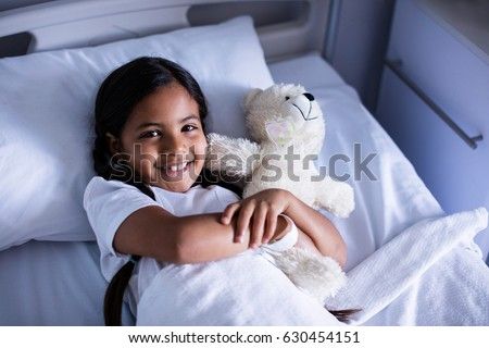Portrait of smiling patient relaxing on bed with teddy bear in hospital