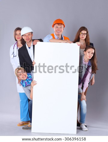 Portrait of smiling people with various occupations holding blank billboard