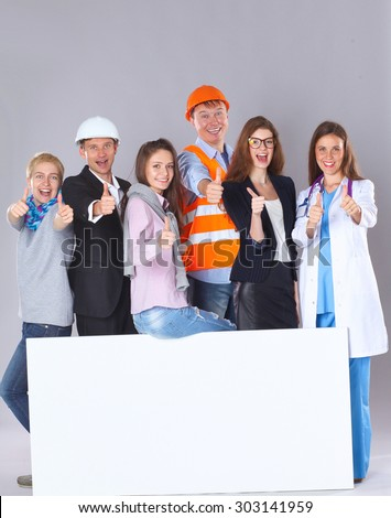 Portrait of smiling people with various occupations holding blank billboard showing ok