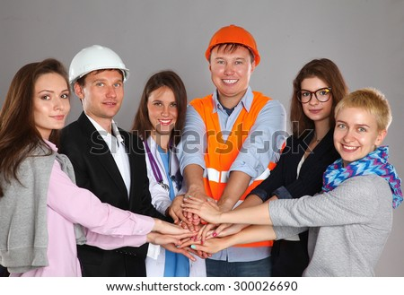 Portrait of smiling people with various occupations putting their hands on top of each other