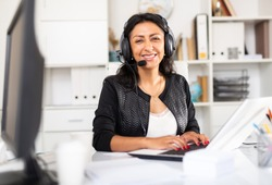 Portrait of smiling Peruvian woman helpline operator with headphones during work in call center
