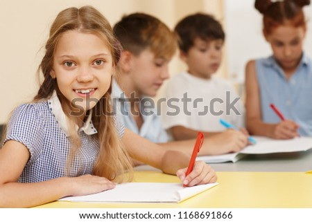 Portrait of smiling pretty girl learning and doing test during lesson on interesting courses. Clever girl sitting at table, looking at camera and posing. Pupils studying on background. #1168691866