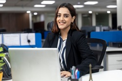 Portrait of smiling pretty Indian businesswoman sitting at her workstation against office background, working on laptop, corporate environment,