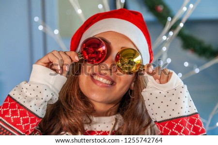 portrait of smiling pretty woman playing with shiny christmas balls on eyes #1255742764