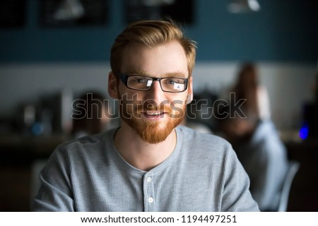Portrait of smiling red haired millennial man looking at camera sitting in café or coffeeshop, happy young male in glasses posing for picture working at laptop or studying out in coffeehouse