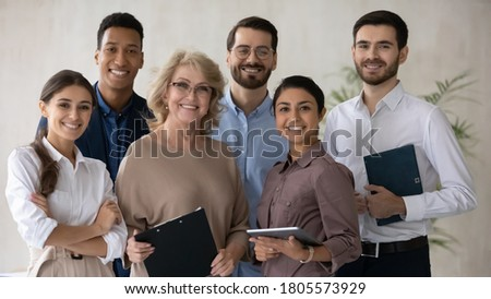 Portrait of smiling 60s middle aged mature female mentor standing in office with motivated skilled young mixed race staff of international company, happy diverse business people looking at camera.