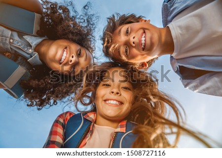 Portrait of smiling school kids standing in cecrle at school yard with look in camera