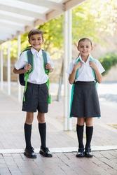 Portrait of smiling school kids standing in corridor at school